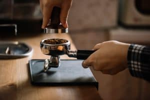 barista tamping coffee